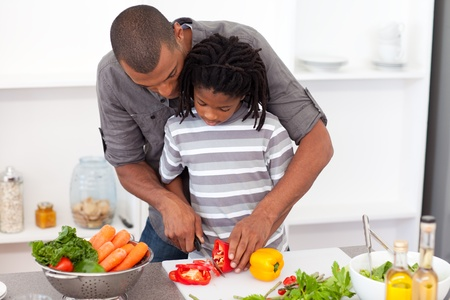 Loving father helping his son cut vegetables photo