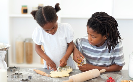 ni�os cocinando: Hermano concentrado y hermana cocinar galletas  Foto de archivo