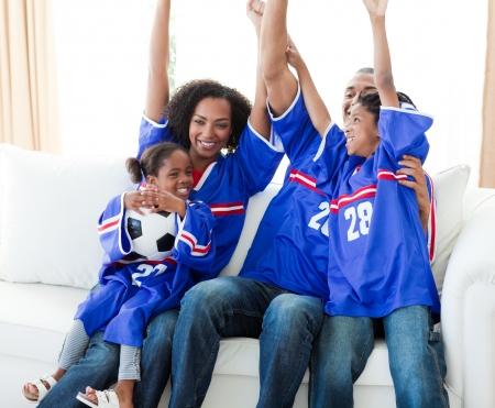 Excité la famille afro-américaine pour célébrer un but de football Banque d'images