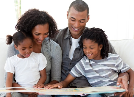kid reading: Afro-American family reading a book in the living-room Stock Photo