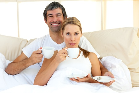 pareja en la cama: Pareja �ntima beber caf� tumbado en la cama Foto de archivo