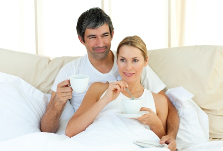 Happy couple drinking coffee lying in the bed photo