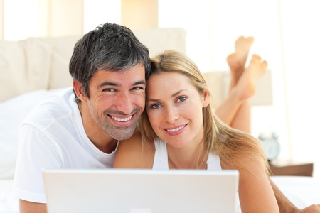 enamoured: Enamoured couple using a laptop lying on bed