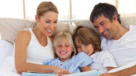 Joyful family reading a book on bed photo