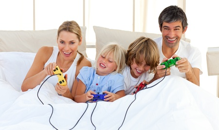 Adorable family playing video game in the bedroom photo