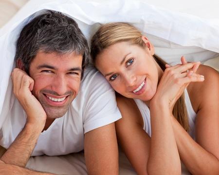parejas felices: Amante de la pareja teniendo diversión acostado en la cama Foto de archivo