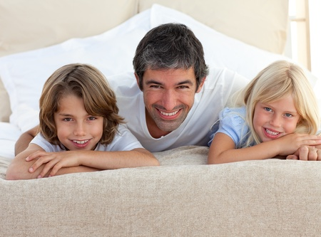 Caring father and his children lying on a bed photo