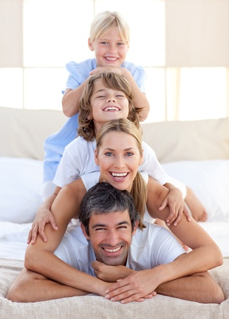 Happy family having fun on a bed photo