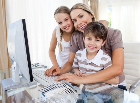 Attractive mother teaching her children how to use a computer  photo