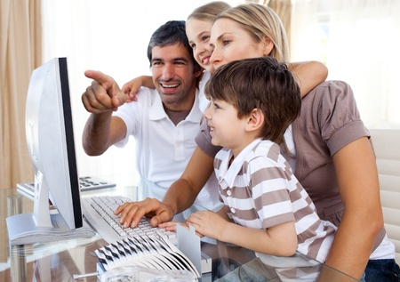 Children learning how to use a computer with their parents Stock Photo - 10110814