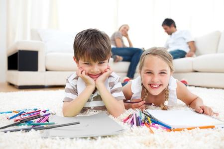 Smiling siblings drawing lying on the floor photo