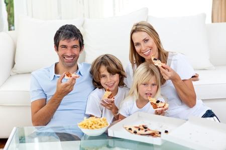 familia comiendo: Alegres niños comiendo una pizza con sus padres Foto de archivo