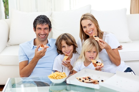 Cheerful children eating a pizza with their parents photo