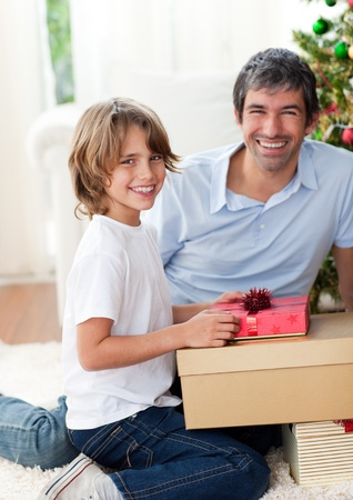Smiling father and his son opening Christmas presents  photo