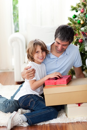Little boy opening Christmas gifts with his father photo