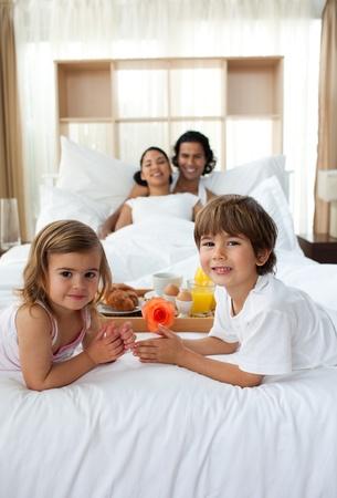despertarse: Hermanos desayunando con sus padres