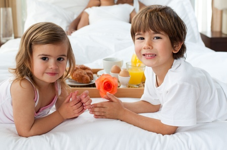 Close-up of cute brother and sister having breakfast with their parents photo