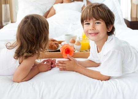 Close-up of siblings bringing breakfast to their parents photo