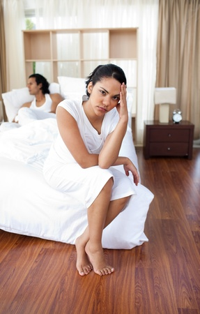 Upset lovers sitting on the bed separately Stock Photo - 10095084