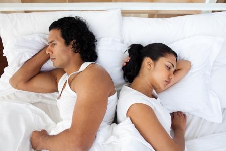 novios enojados: Molesta pareja en la cama durmiendo por separado