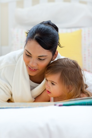 Attentive mother reading with her daughter  Stock Photo - 10094928