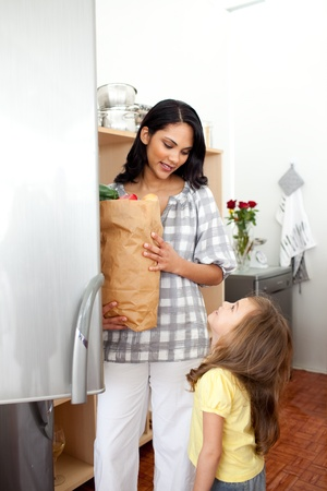 Cheerful little girl unpacking grocery bag with her mother photo
