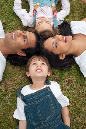 Lively family lying in a circle on the grass  photo