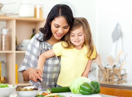 Blond child cutting vegetables with her mother photo
