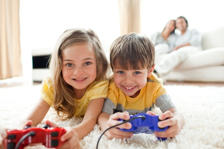 niños jugando videojuegos: Amorosos hermanos jugando videojuegos