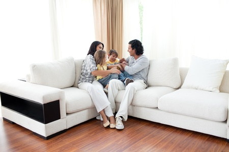 family in living room: Animated family having fun sitting on sofa Stock Photo