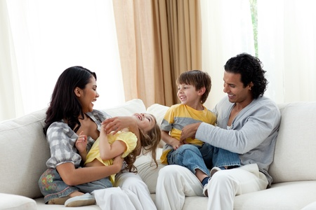 earing: Earing parents playing with their children on sofa Stock Photo