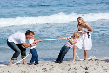 tug: Cheerful family playing tug of war Stock Photo