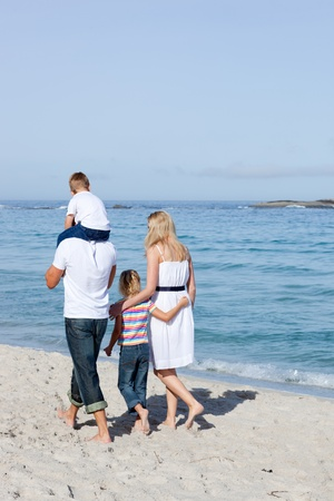 Cheerful family walking on the sand  photo