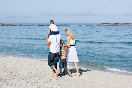 Affectionate family walking on the sand  photo