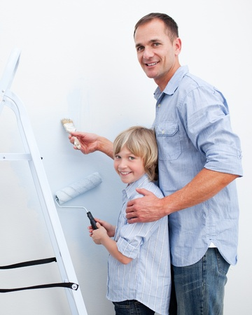 Smiling father and his son holding paintbrush photo