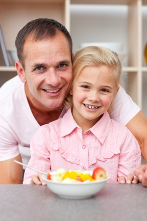 Happy little girl eating fruit with her father  photo