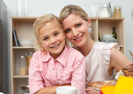 Cute little girl in the kitchen with her mother  photo