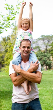 Joyful father giving his daughter piggy-back ride  photo