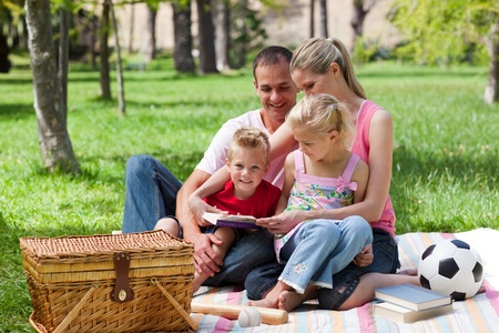 Young family relaxing while having a picnic photo