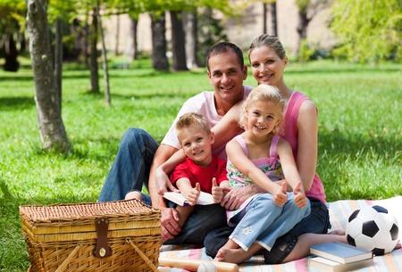 Family having a picnic smiling at the camera photo