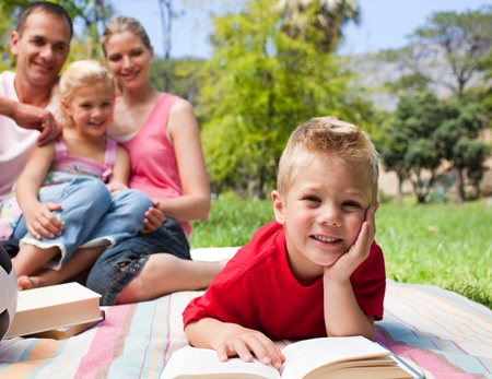 Smiling little boy reading lying on the grass while having a picnic with his family photo