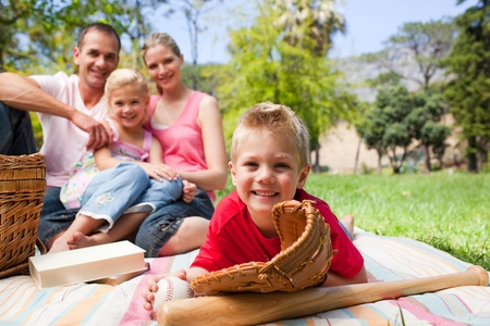 Smiling little boy wearing a baseball glove while having a picnic with his family photo