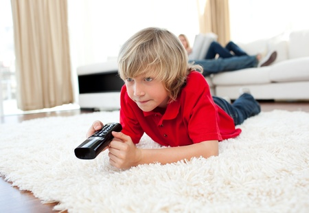 Cute boy holding a remote lying on the floor  photo