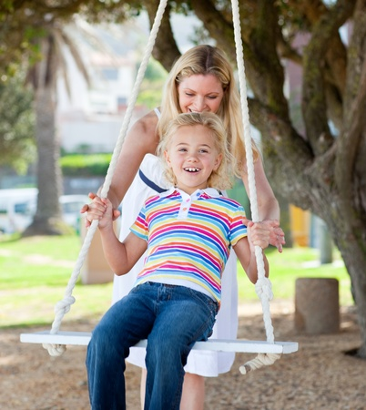 casually: Happy mother pushing her daughter on a swing Stock Photo
