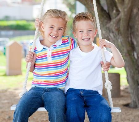 Cute siblings swinging Stock Photo - 10091834