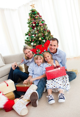 Portrait of a smiling family holding Christmas presents photo
