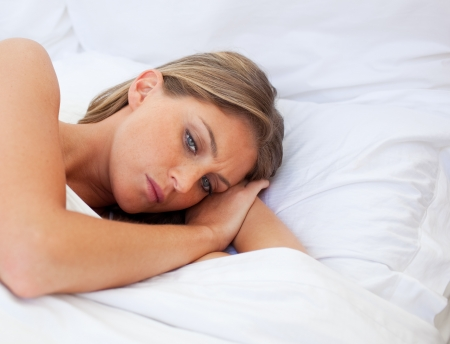 relationship problems: Worried woman lying on her bed  Stock Photo
