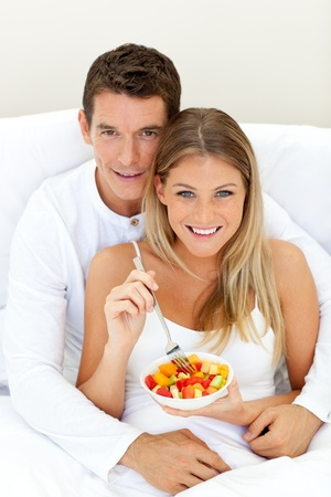 Loving couple eating fruit lying on their bed  photo