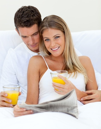 Loving couple reading a newspaper and drinking orange juice  photo