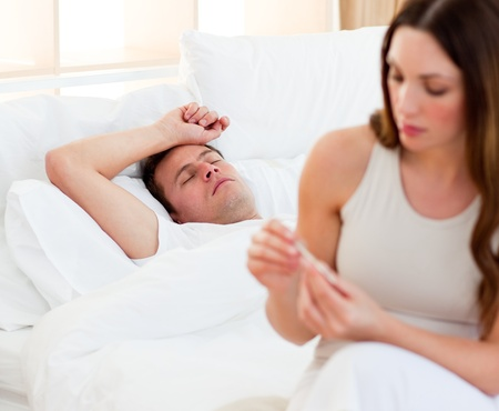 taking a wife: Concerned woman taking her sick husbands temperature Stock Photo